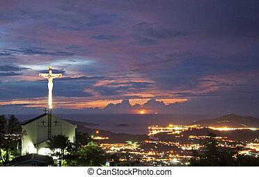 St. Joseph Church of Menggatal, Kota Kinabalu, Sabah, Malaysia during sunset with city lights as background.