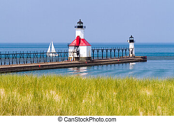 St. Joseph, Michigan North Pier Lighthouses with a Sailboat on Lake Michigan.