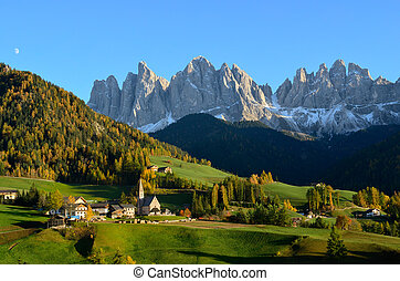 St. Magdalena or Santa Maddalena with its characteristic church in front of the Geisler or Odle Dolomites mountain peaks in the Val di Funes (Villnosstal) in Italy in autumn.