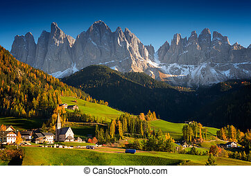 St. Magdalena or Santa Maddalena village with its church in front of the Geisler Dolomites mountain peaks in the Val di Funes Valley (Villnoesstal) in South Tyrol, Italy in autumn.