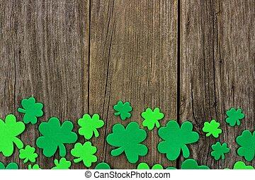 St Patricks Day bottom border of shamrocks over rustic wood...