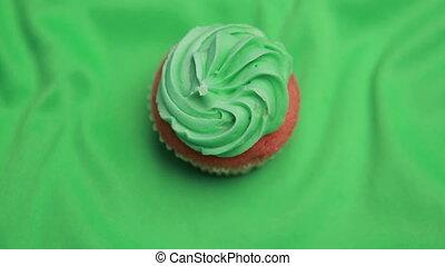 St patricks day cupcake revolving on green surface