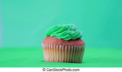 St patricks day cupcake spinning around on green background