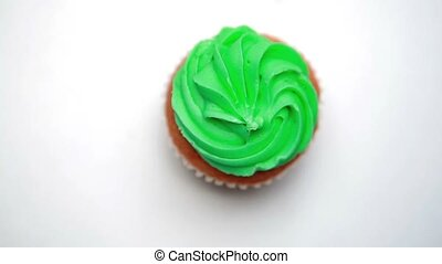 St patricks day cupcake turning with sprinkles falling on...