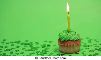 St patricks day cupcake with shamrock confetti burning...