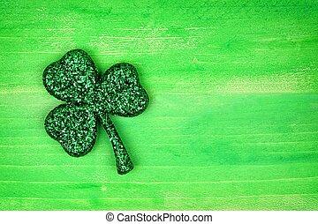 St Patricks Day glittery shamrock over green wood