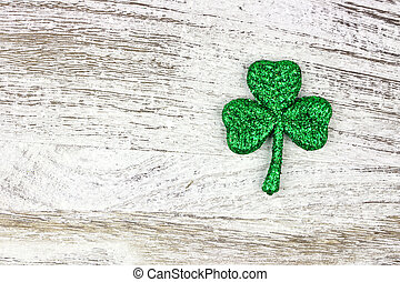 St Patricks Day glittery shamrock over rustic white wood