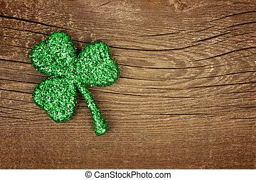 St Patricks Day glittery shamrock over wood