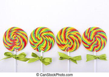 St Patricks Day Rainbow Lollipops on white wood table...