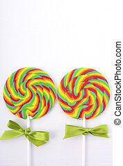 St Patricks Day Rainbow Lollipops on white wood table flat...