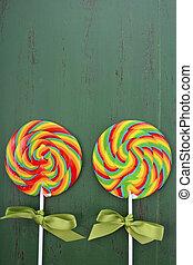 St Patricks Day Rainbow Lollipops on dark green wood table...