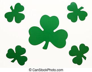 five green paper shamrocks arranged over white