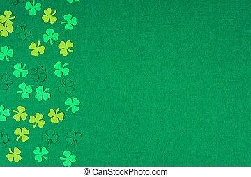 St Patricks Day shamrocks side border over a green background