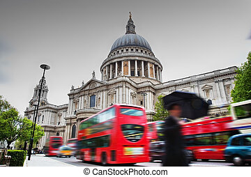 St Paul's Cathedral in London, the UK. Red buses in motion...