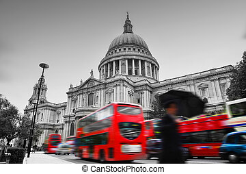 St Paul's Cathedral in London, the UK. Red buses in motion