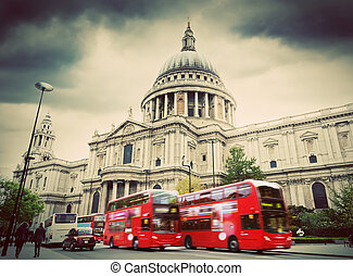 St Paul's Cathedral in London, the UK. Red buses in motion, vintage, retro style