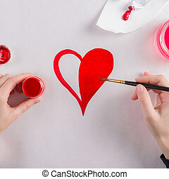 St. Valentine's Day background. Girl drawing with paints heart on white background.