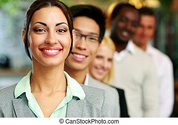 staand, businesswoman, collega's, het glimlachen, voorkant