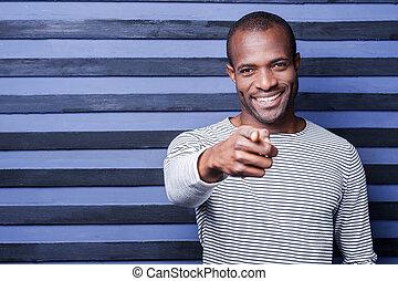staand, gelukkig glimlachen, wijzende, jonge, tegen, terwijl, you!, achtergrond, afrikaan, gestreepte , man, u, kiezen