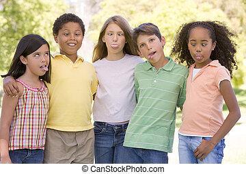 staand, grappige gezichten, jonge, vijf, buitenshuis, het maken van vrienden