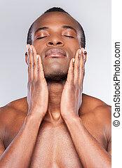staand, het behouden, zijn, achtergrond, jonge, shirtless, afrikaan, eyes, tegen, grijze , terwijl, aandoenlijk, gesloten, handen, gevoel, schoonmaken, gezicht, fresh., man