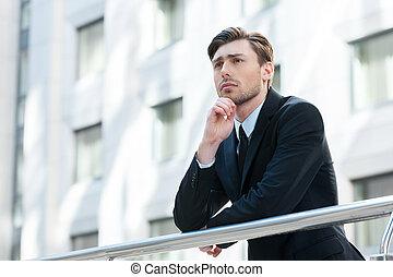staand, het kijken, over, denken, weg, jonge, formalwear, hand, solutions., terwijl, kin, vasthouden, buitenshuis, aanzicht, bovenkant, man