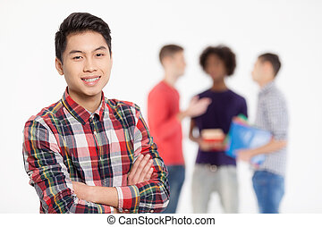 staand, jongen, tiener, zijn, chinees, het behouden, armen, vrolijk, zeker, terwijl, gekruiste, achtergrond, friends., het glimlachen, vrienden