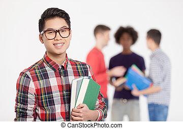 staand, jongen, tiener, zijn, vasthouden, chinees, confident., vrolijk, terwijl, boekjes , achtergrond, het glimlachen, vrienden, smart, bril