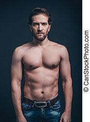 staand, shirtless, confident., jonge, tegen, gezicht, het kijken, terwijl, fototoestel, zwarte achtergrond, serieuze , sterke man