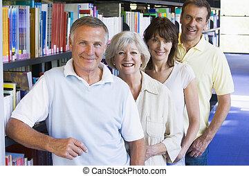 staand, vier, bookshelves, bibliotheek, mensen