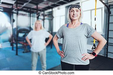 staand, vrouw, gym, handen, het glimlachen, heupen