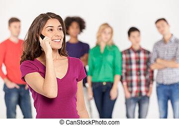 staand, vrouw het spreken, beweeglijk, always, jonge, vrolijk, telefoon, terwijl, zijn, achtergrond, vrienden, touch.