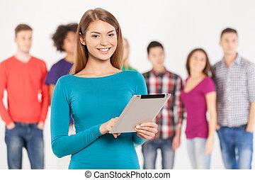 staand, vrouw, toevoegen, vasthouden, tablet, jonge, vrolijk, age., terwijl, zijn, achtergrond, digitale , vrienden