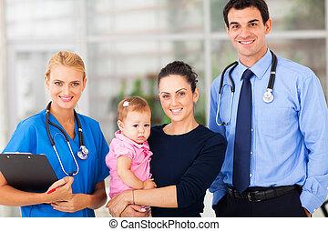 staand, vrouw, vrouwlijk, haar, arts, vasthoudende baby, verpleegkundige