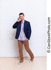staand, zakelijk, muur, op, cel telefoongesprek, zakenman, spreken, smartphone, man
