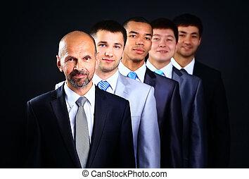 staand, zakelijk, op, gevormde, jonge, donker, zakenlieden, achtergrond, de leider van het team