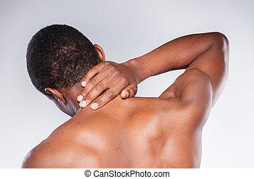 staand, zijn, hals, shirtless, pain., jonge, tegen, grijze , terwijl, aandoenlijk, achtergrond, afrikaan, aanzicht, achterkant, man