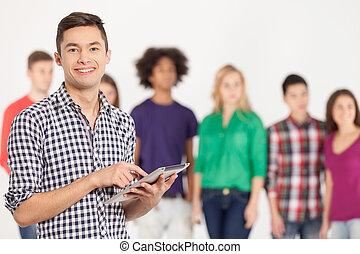 staand, zijn, toevoegen, vasthouden, tablet, jonge, vrolijk, age., terwijl, achtergrond, digitale , vrienden, man