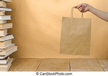 brown kraft bag - stack book on wooden table and brown kraft...