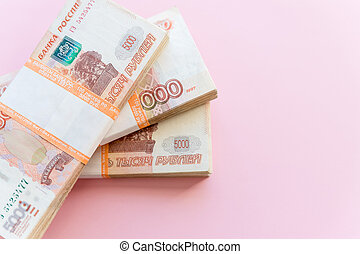 Stack of 5000 rubles packs isolated on pink. The concept of wealth, profits, business and finance. Stack money in the five thousandth bills banknotes. A lots wads of money, many cash