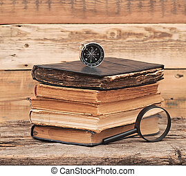 Stack of antique books with compass and magnifying glassl on wood background