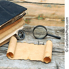 Stack of antique books with compass, magnifying glass and...