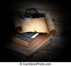 Stack of antique books with compass, magnifying glass and paper scroll on wood background