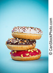 Stack of assorted donuts on pastel background.
