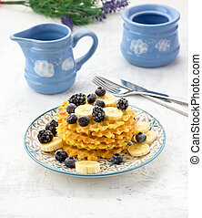 stack of baked Belgian waffles on a round plate with berries on a white table