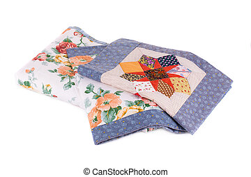 Stack of beautiful handmade quilts. Isolated on a white...