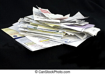A huge stack of bills and receipts on black background.