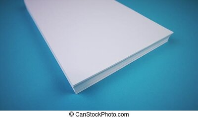 stack of new white blank paper sheets lies on light blue table fabric extreme close travelling cam
