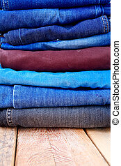 Stack of blue and black jeans on wooden background