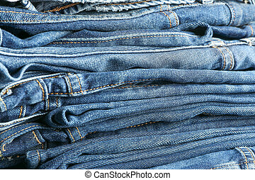 Stack of blue jeans as background, space for text